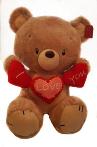 Brown Teddy bear holding I love you sign