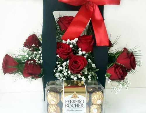 Red Roses arranges in a box with a red bow with Chocolates on the side